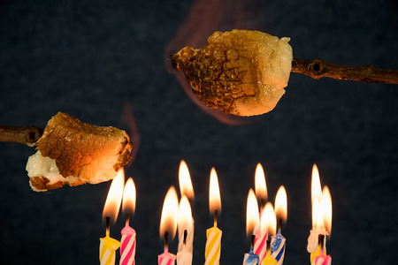 close up of roasting marshmallows over birthday cake candles Stock Photo