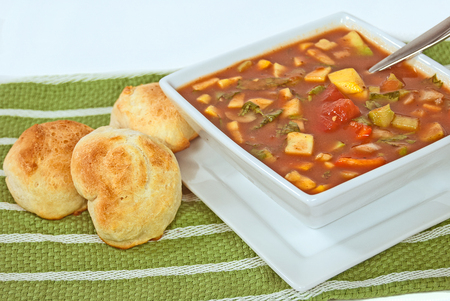 gazpacho soup in white square bowl with dinner rolls on green cloth