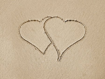 pair of hearts drawn in beach sand