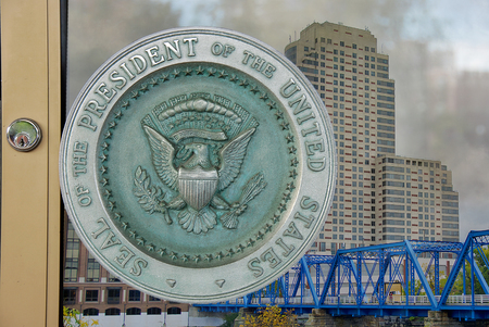close up of Presidential seal on glass door with Grand Rapids city reflection background Stock Photo