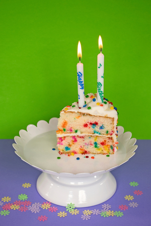 slice of birthday cake with candle on white pedestal plate and confetti Stock Photo
