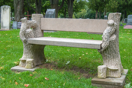 vacant stone bench in cemetery on grass