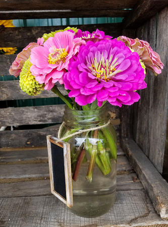 bright colored gerbera daisy bouquet in mason jar with chalkboard tag on string