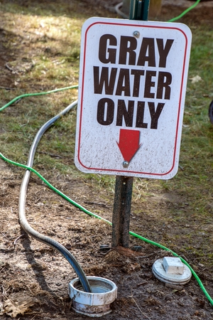 gray water warning sign on metal post in dirt with dirty hoses Stock Photo