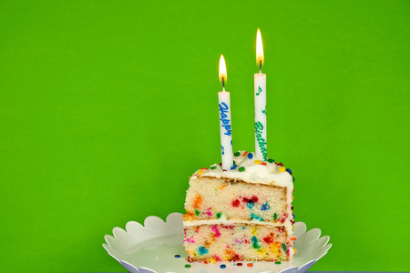 slice of birthday cake with candles on neon green background