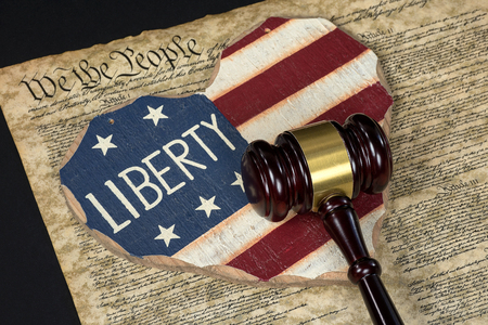 wooden flag heart on United States constitution document with court gavel Stock Photo