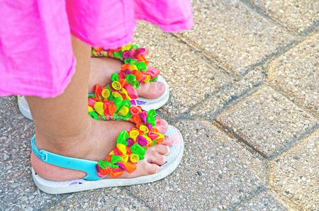 close up of little girl in pink dress wearing balloons on flip-flops