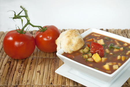 gazpacho soup in white square bowl with dinner rolls on bamboo place mat