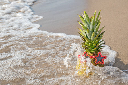 Pineapple on sandy beach with red star sunglasses splashed by wave