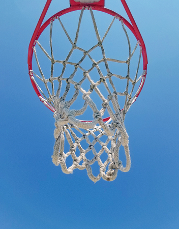 underside view of basketball hoop with bright blue sky background Stock Photo