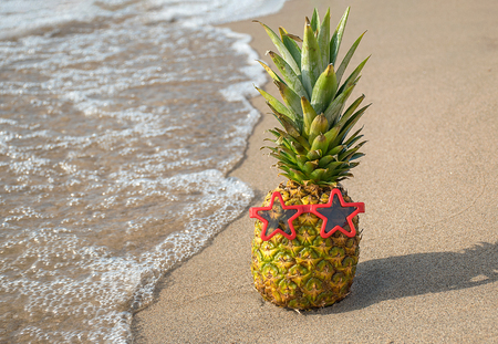 Tropical pineapple with red star sunglasses on sandy beach