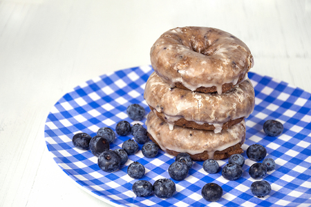 blueberry donut stack with berries on blue and white checked plate on wood
