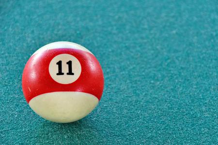 close up of billiard ball number eleven on green felt