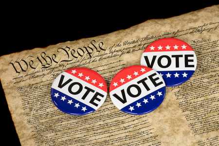 Patriotic campaign voting pins on vintage United States Constitution document Stock Photo