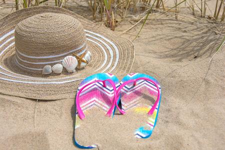 hat and summer flip-flops in beach sand