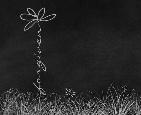 Forgiven text daisy flower in grass on black chalkboard