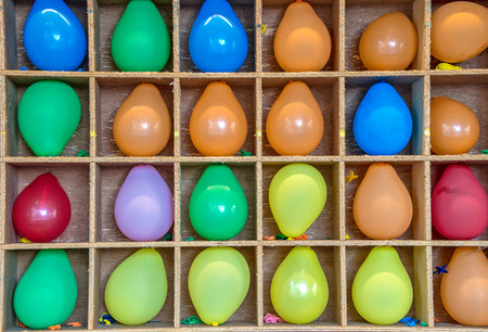 colorful inflated balloons in wooden box frame for carnival game Stock Photo