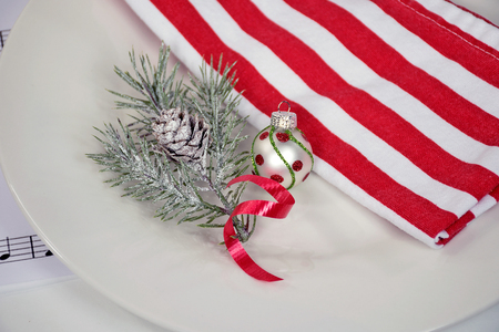 holiday pine with Christmas ornament and red and white stripe cloth dinner napkin on plate