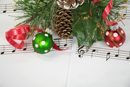 red and green Christmas ornaments and ribbon with pine on sheet music