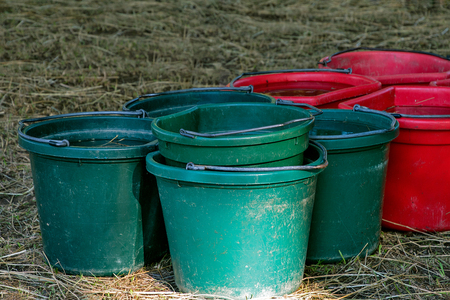 Red and green buckets of water on straw in barn