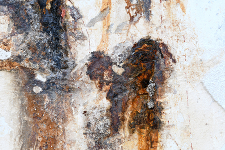 Close up of peeling paint and rusty stain on wall
