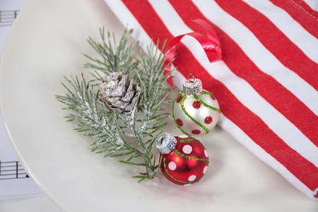 holiday pine and Christmas ornament on white dinner plate with striped cloth napkin
