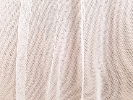 close up of blush colored sheer tulle fabric