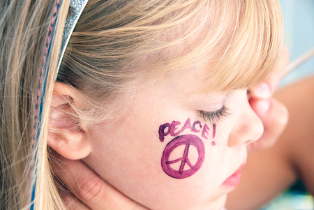 young blond girl with face painted peace sign on cheek