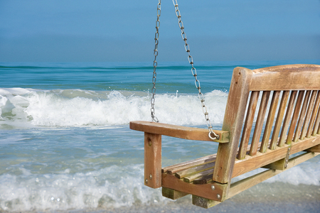 rustic wooden beach swing with turquoise ocean surf view Stock Photo