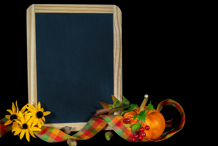autumn pumpkin with black-eyed Susan floral bouquet and blank black chalkboard Stock Photo