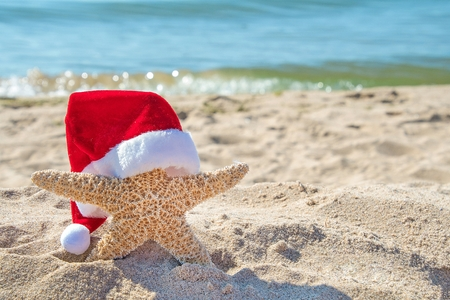 Christmas hat on starfish in beach sand with ocean water background