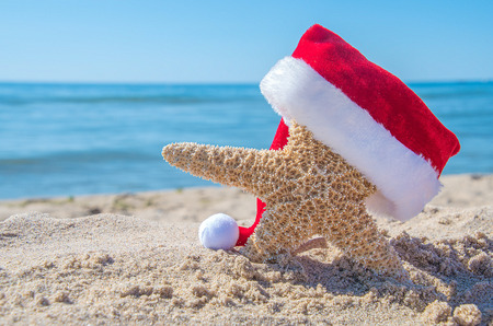 starfish with Christmas Santa cap in beach sand with water background