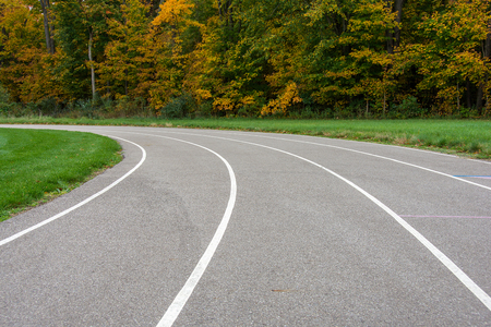 vacant sports track with white lines curving into autumn trees Stock Photo