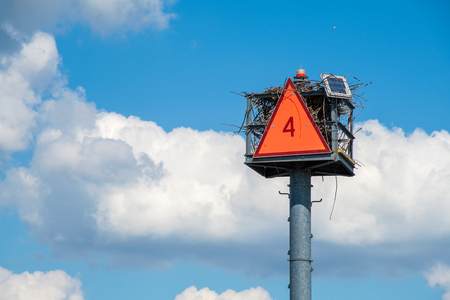 empty osprey nest in navigational buoy with a bright orange number 4 triangle sign