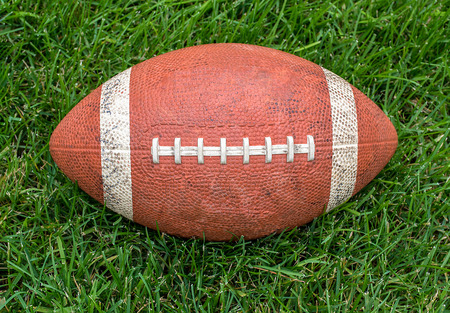 used brown football on green playing field