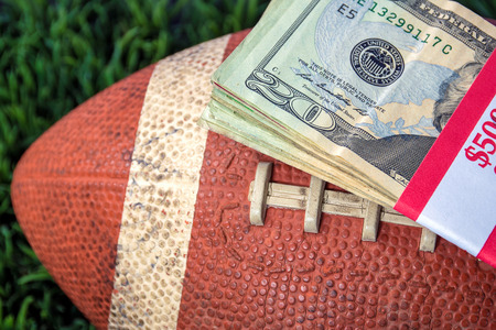 close up of wrapped money stack on used football with green grass background
