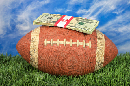 wrapped money stack on American football with sky background on grass Stock Photo
