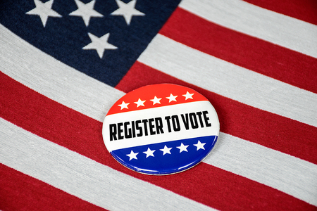 close up of register to vote election button on American flag