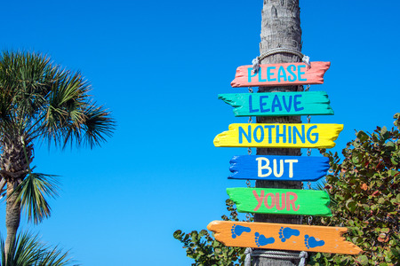 colorful wooden beach sign on palm tree trunk in Florida Stock Photo