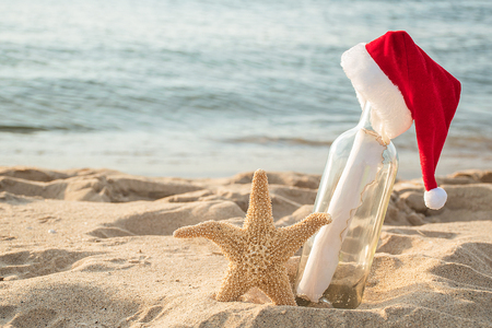 red and white fur Christmas hat on message in a bottle with starfish in beach sand with water background