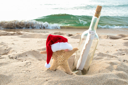 starfish in beach sand with holiday Santa hat and message in a bottle