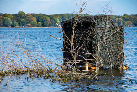 duck blind camouflaged with dark mesh and tree branches in lake water Stock Photo