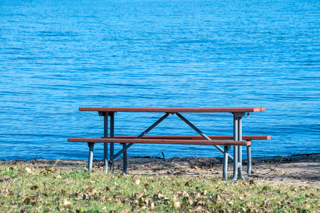 vacant picnic table in sand and grass by blue lake water Stock Photo