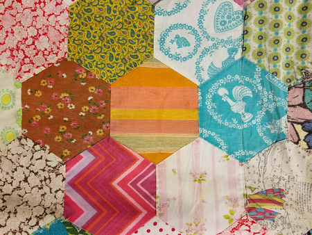 close up of homemade patchwork quilt with hexagon shape fabric pieces
