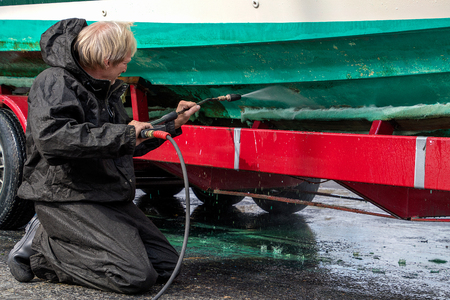 Caucasian man kneeling while high pressure washing dirty boat hull on red trailer Stock Photo