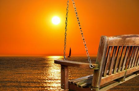 empty hanging wooden swing overlooking sunset on lake Stock Photo