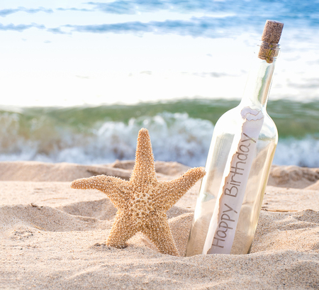 close up of starfish and happy birthday message in a bottle on the seashore with water background Stock Photo