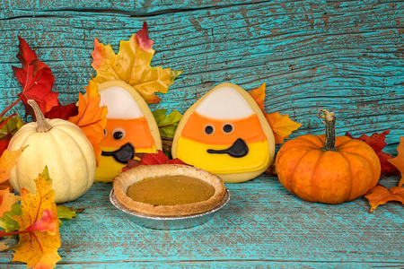 Candy corn sugar cookies and pumpkin pie with autumn pumpkins on turquoise colored rustic wood Stock Photo