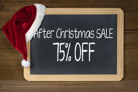 After Christmas sale sign on black chalkboard with red and white fur Santa hat