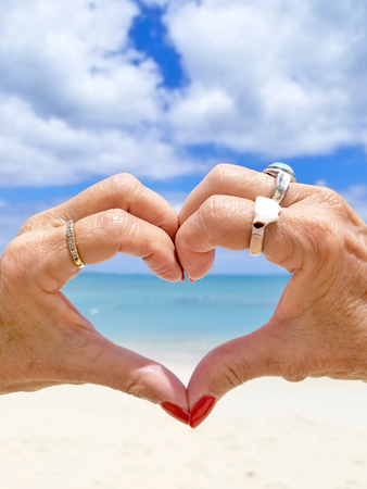 pair of hands using fingers to form a heart with view of tropical beach and ocean Stock Photo
